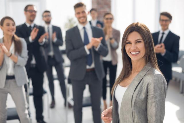 笑顔で拍手するビジネスマンたち